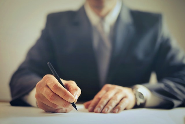 man in suit writing document feature